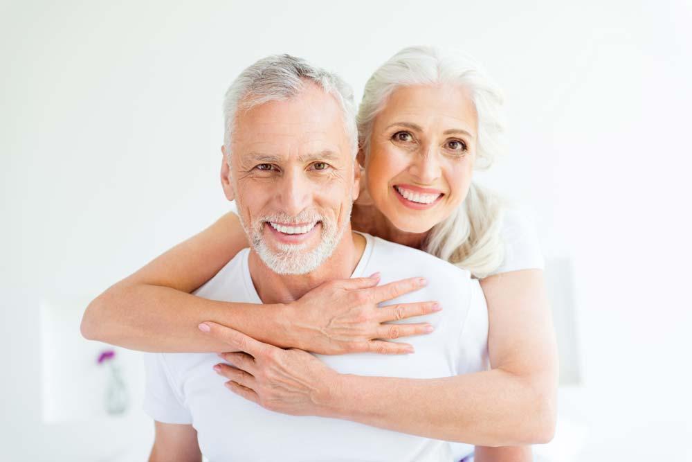 Das Bild zeigt einen Mann und eine Frau mit festen dritten Zähnenn