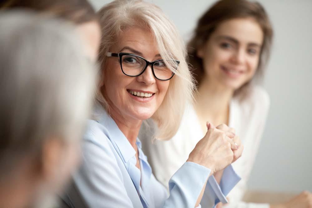 Eine Nahaufnahme einer Frau mittleren Alters im Berufsleben mit gepflegten Zähnen