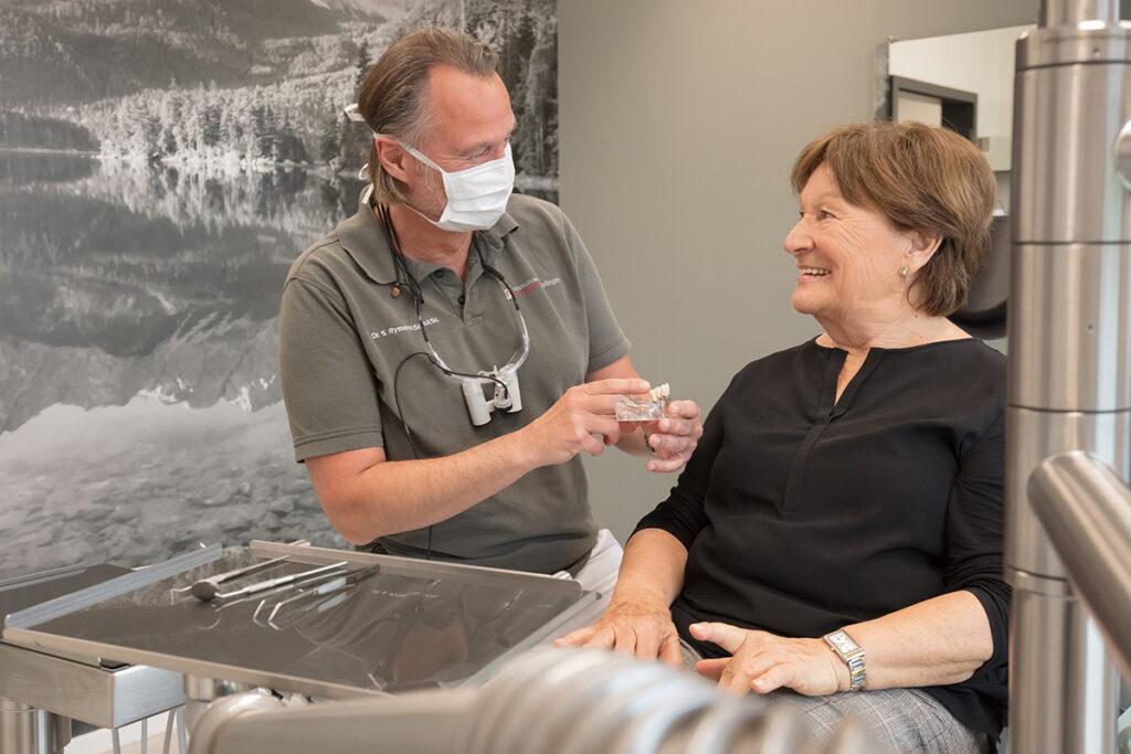 Das Foto zeigt Dr. Ryssel im Beratungsgespräch zu Implantaten mit einer Patientin.