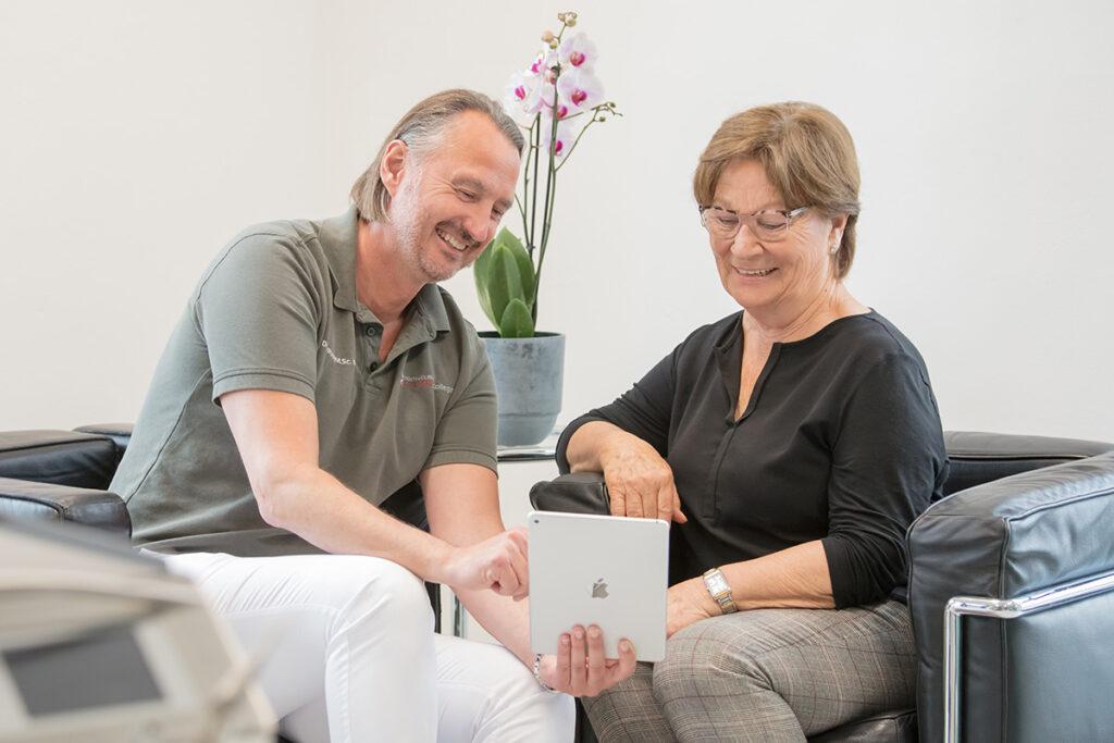 Das Foto zeigt den Zahnarzt und Implantologen Dr. Rysell im Gespräch mit einer Patientin